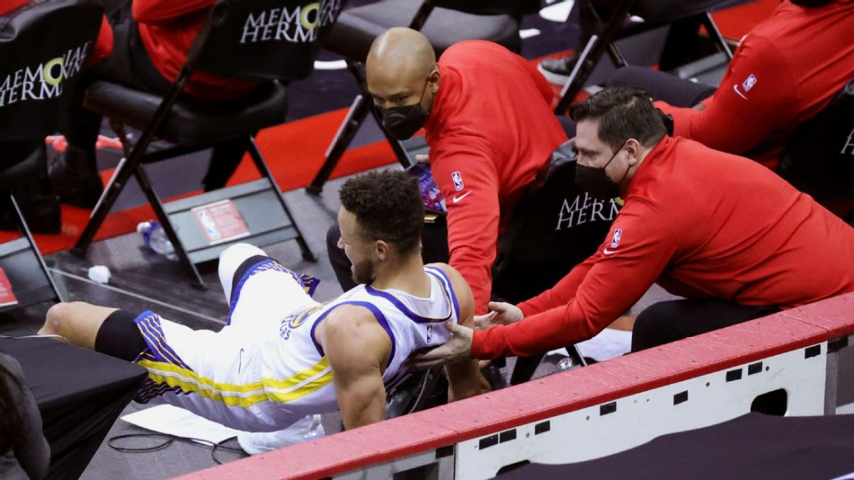 Stephen Curry cade di fianco alla panchina dei Rockets