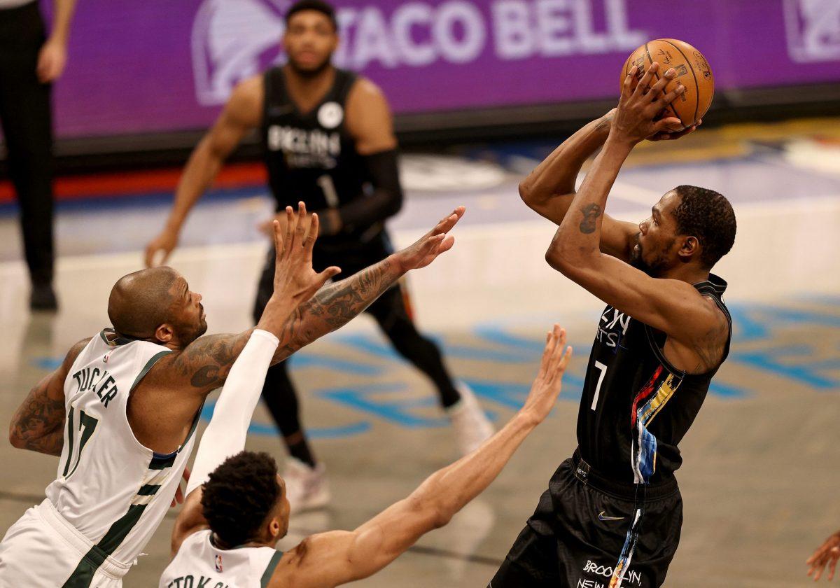 Kevin Durant al tiro contro due difensori dei Milwaukee Bucks